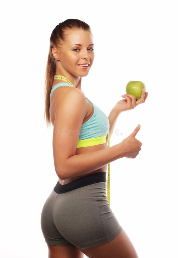 Спорт, диета, здоровье и концепция людей: Молодая жизнерадостная женщина в спорт носит с яблоком, изолированным над белой предпос стоковые фотографии rf