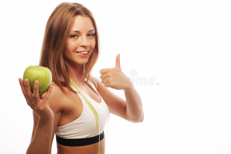 Спорт, диета, здоровье и концепция людей: Молодая жизнерадостная женщина в спорт носит с яблоком, изолированным над белой предпос стоковое изображение rf