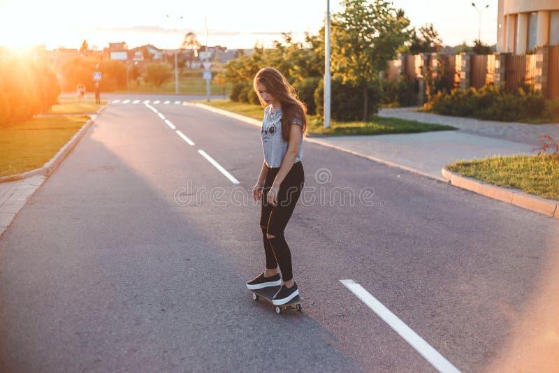 Спорт лета и активный образ жизни Холодный скейтборд катания конькобежца маленькой девочки на улице заходом солнца напольно стоковая фотография
