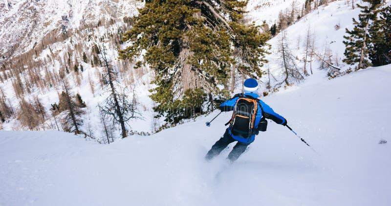 Спорт зимы: катание на лыжах человека в снеге порошка стоковое фото rf