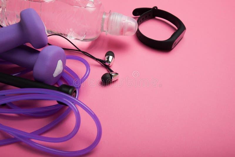 Спорт и атлетика, гантель и прыгая веревочка с браслетом фитнеса на розовой предпосылке r стоковое фото rf