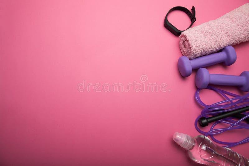Спорт и атлетика, гантель и прыгая веревочка с браслетом фитнеса на розовой предпосылке r стоковые фото