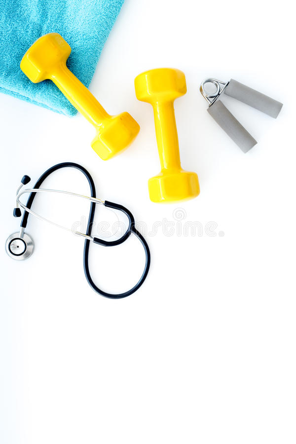 Спорт и здоровье Фитнес Гантели и стетоскоп на белом copyspace взгляд сверху предпосылки стоковая фотография rf