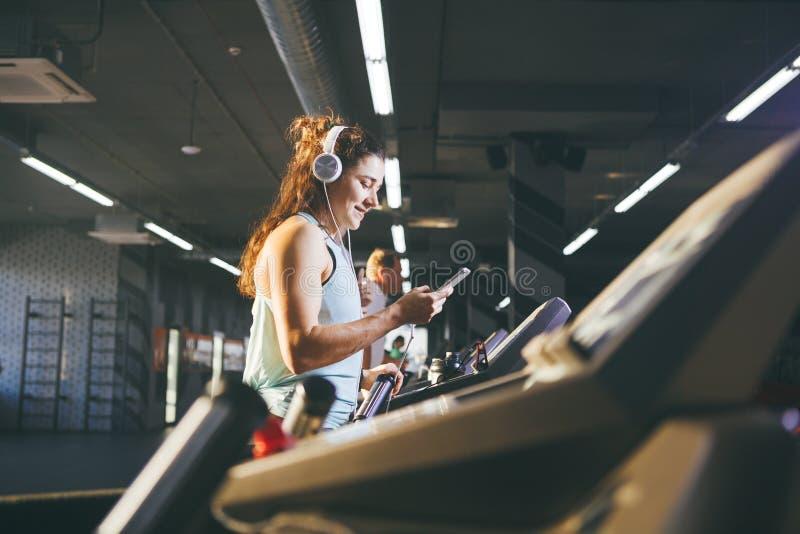 Спорт и музыка темы Красивая кавказская женщина бежать в спортзале на третбане На головных больших белых наушниках, девушка слуша стоковая фотография rf