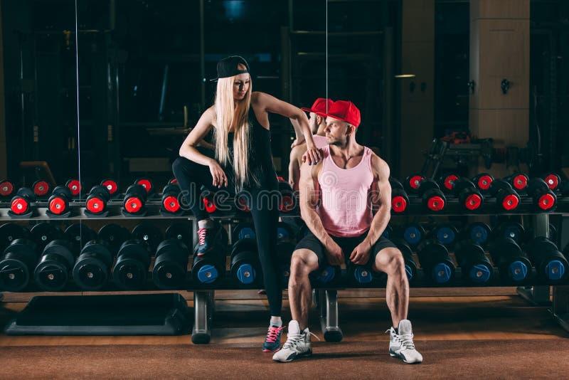 Спорт, культуризм, поднятие тяжестей, образ жизни и концепция людей - молодая красивая пара в стильных одеждах сидя a стоковая фотография rf