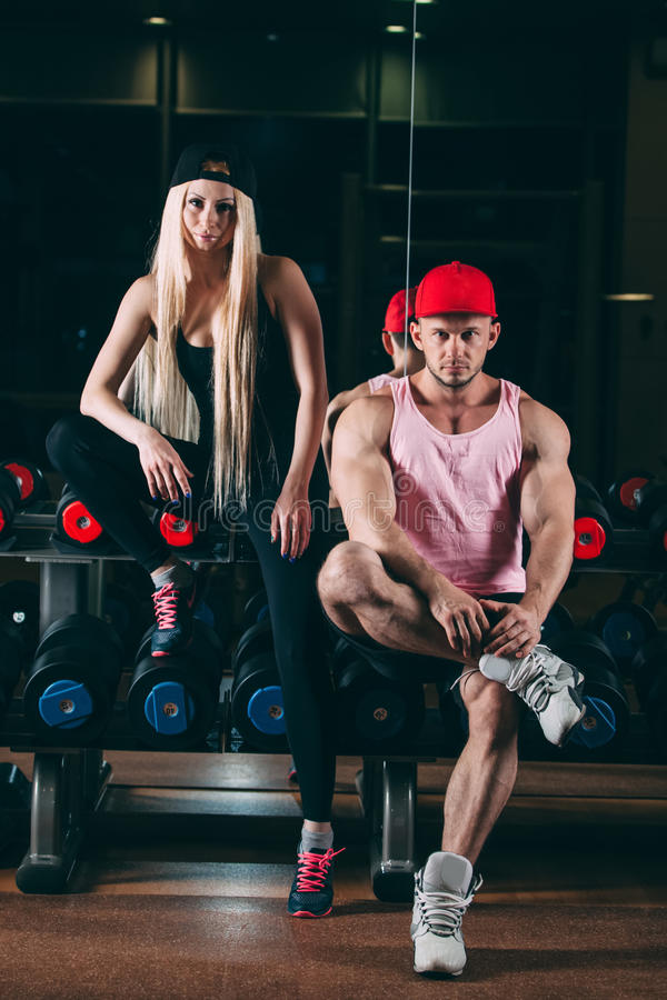Спорт, культуризм, поднятие тяжестей, образ жизни и концепция людей - молодая красивая пара в стильных одеждах сидя a стоковое изображение rf