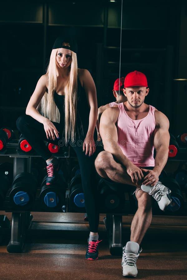 Спорт, культуризм, поднятие тяжестей, образ жизни и концепция людей - молодая красивая пара в стильных одеждах сидя a стоковые фото