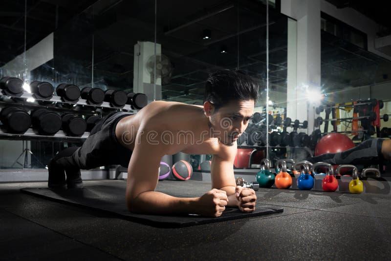 Спорт Молодой атлетический делать человека нажим-поднимает Мышечный и сильный парень работая, портрет красивого человека делать н стоковое фото
