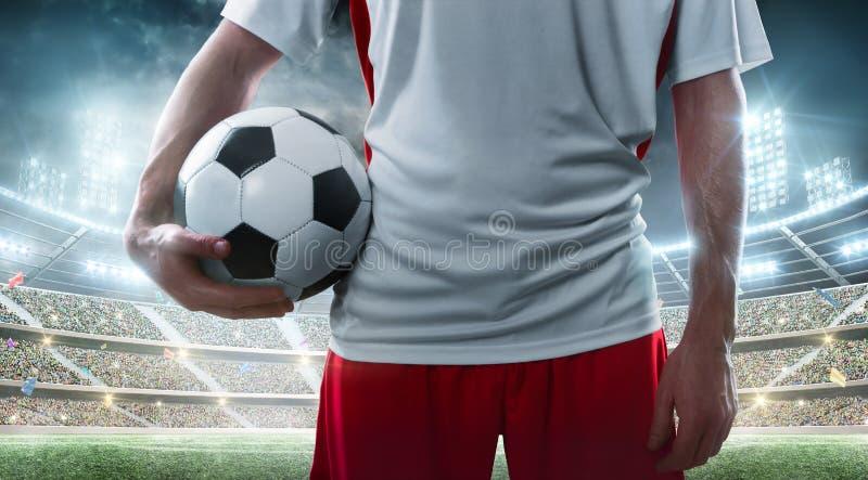Спорт Профессиональный футболист держа футбольный мяч на предпосылке стадиона конец вверх стоковые изображения rf