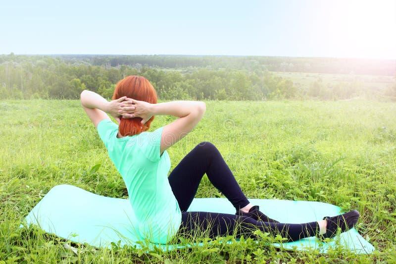 Спорт работая делающ женщину outdoors, на траве стоковые фото