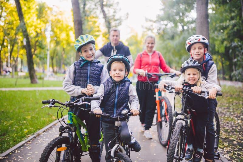 Спорт семьи темы отдыхают в парке в природе большой дружелюбный кавказский горный велосипед людей семьи из шести человек ехать вн стоковая фотография rf