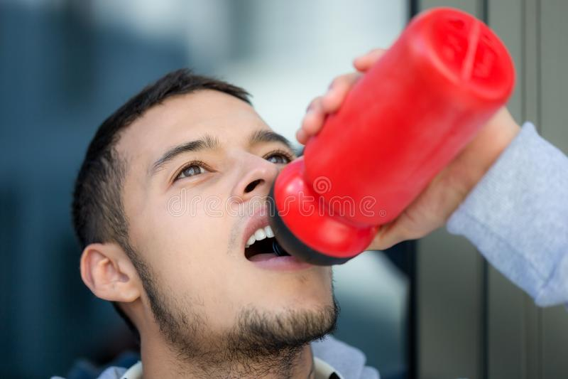 Спорт спорта бегуна молодого человека питьевой воды бежать jogging тренируя фитнес стоковые изображения rf