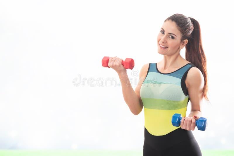 Спорт счастливой девушки фитнеса практикуя делая весы с гантелями стоковые фото