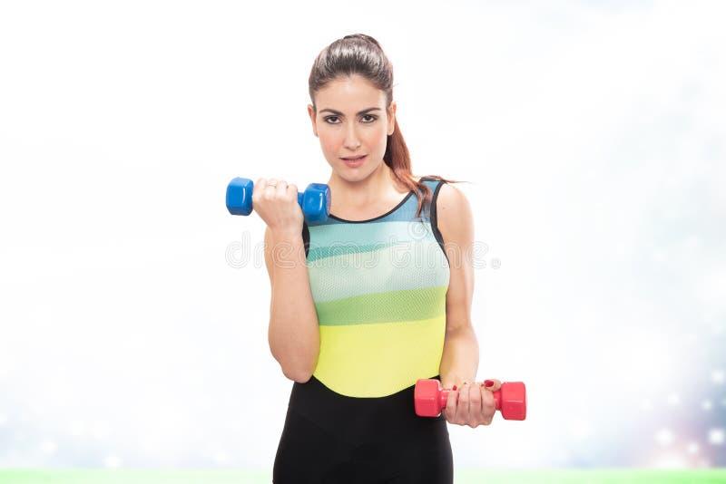 Спорт счастливой девушки фитнеса практикуя делая весы с гантелями стоковое изображение rf