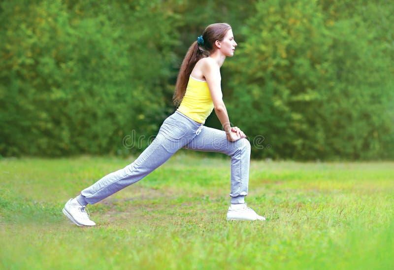 Спорт, фитнес, концепция йоги - молодая женщина делает протягивать стоковое изображение rf