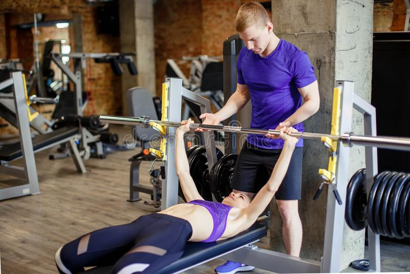 Спорт, фитнес, культуризм и концепция людей - женщина и личный тренер с штангой запирают изгибать мышцы в спортзале стоковое изображение rf