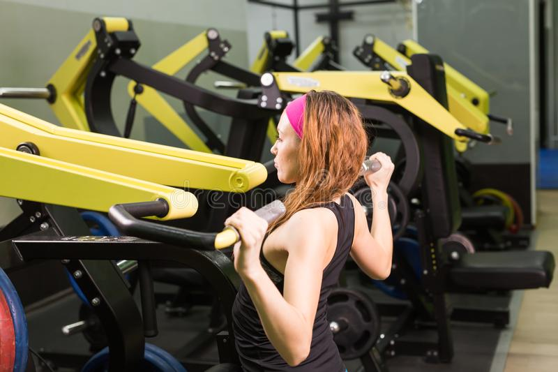 Спорт, фитнес, образ жизни и концепция людей - красивая женщина изгибая мышцы на машине спортзала стоковое фото rf