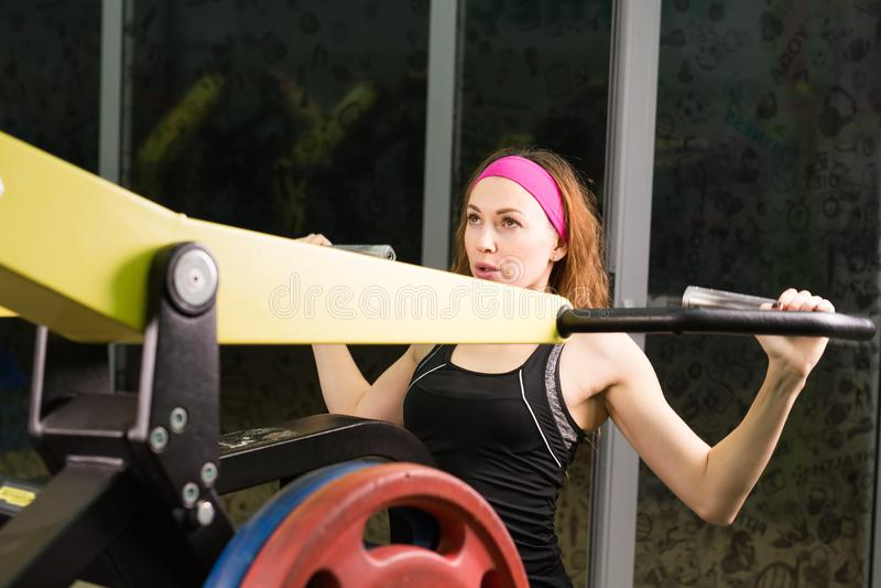 Спорт, фитнес, образ жизни и концепция людей - красивая женщина изгибая мышцы на машине спортзала стоковая фотография rf