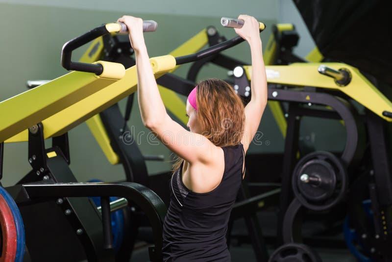 Спорт, фитнес, образ жизни и концепция людей - красивая женщина изгибая мышцы на машине спортзала стоковое изображение rf