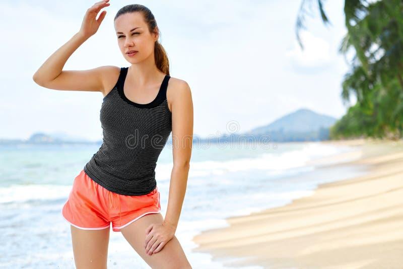Спорт, фитнес Подходящая женщина принимая пролом после бежать Разминка, стоковые изображения