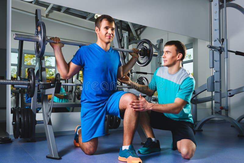 Спорт, фитнес, сыгранность, занимаясь культуризмом концепция людей - человек и личный тренер при штанга изгибая мышцы в спортзале стоковые изображения rf