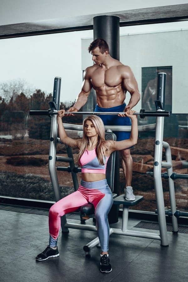 Спорт, фитнес, сыгранность, культуризм и концепция людей - молодая женщина и личный тренер с изгибать штанги стоковые фотографии rf