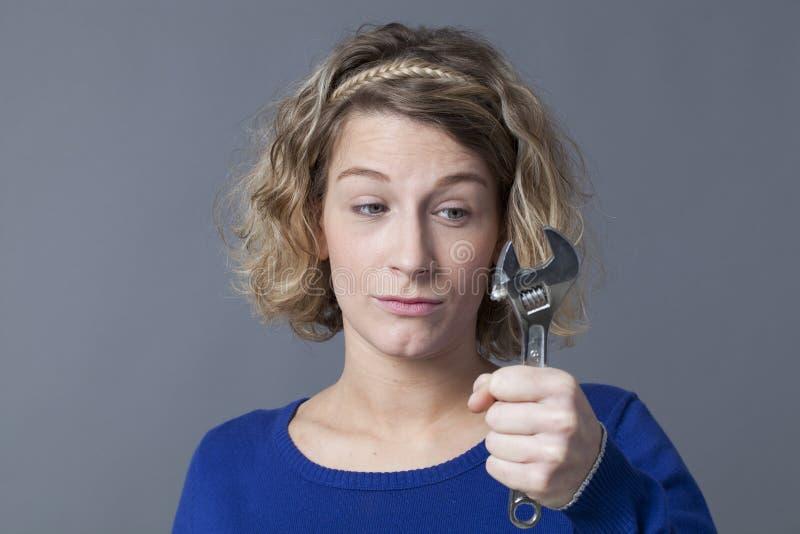 Спрашивая ключ удерживания женщины 20s для механиков DIY стоковое фото rf