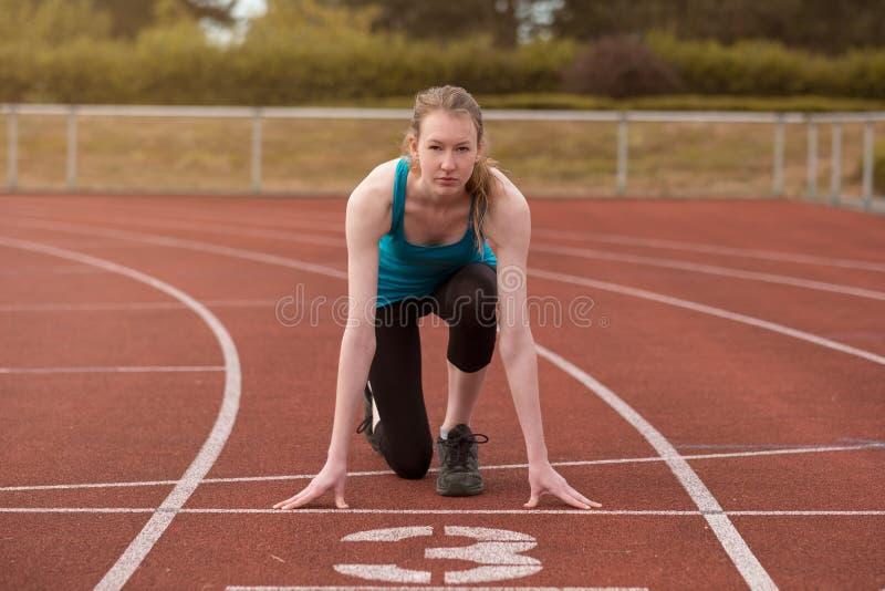 Спринтер молодой женщины в положении стартера стоковые фотографии rf