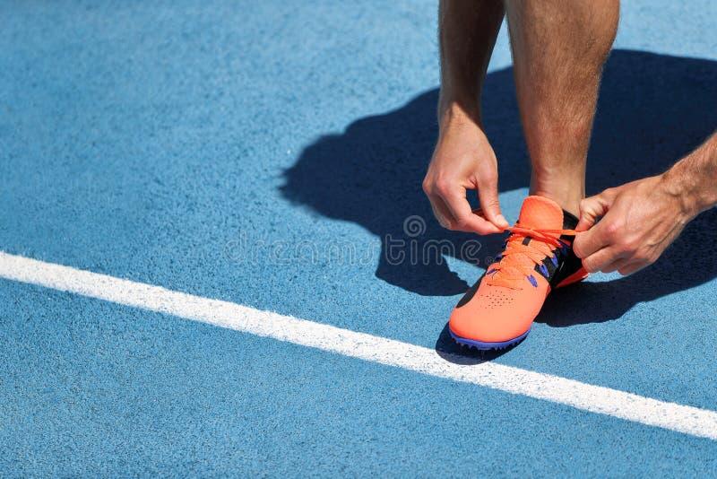 Спринтер спортсмена получая готовый побежать связывать вверх по шнуркам ботинка на следах стадиона бежать Бегун человека подготав стоковое фото rf