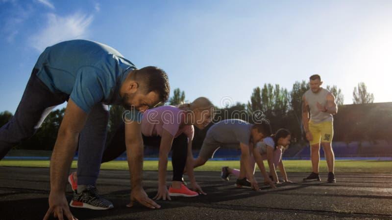 Спринт семьи идущий на время на стадионе стоковые фотографии rf