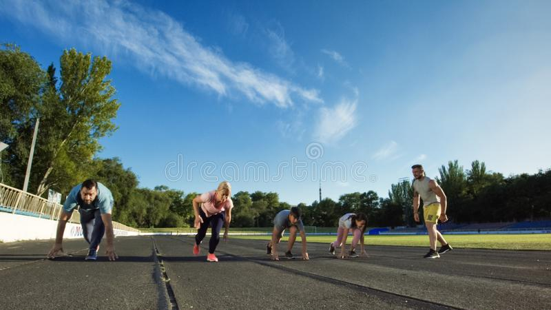 Спринт семьи идущий на время на стадионе стоковые изображения rf