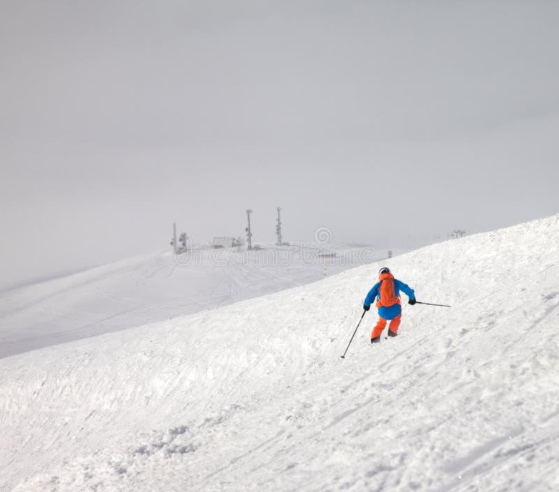 Спуск лыжника на снежный наклон freeride и небо overcast туманное стоковые изображения rf