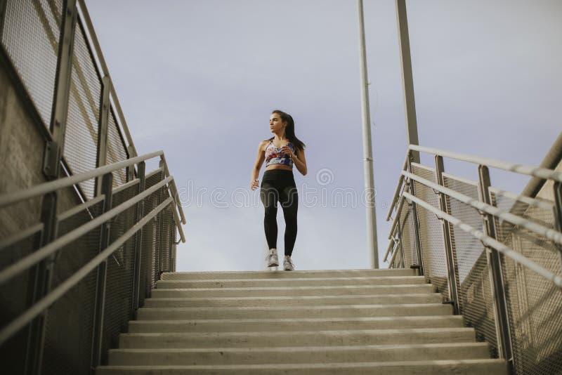 Спуск молодой женщины бежать один лестницы стоковые изображения rf