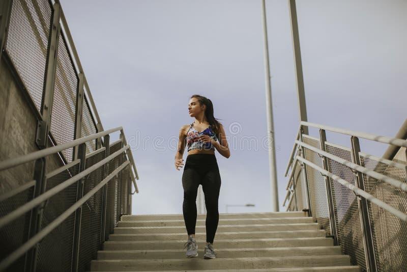 Спуск молодой женщины бежать один лестницы стоковое изображение