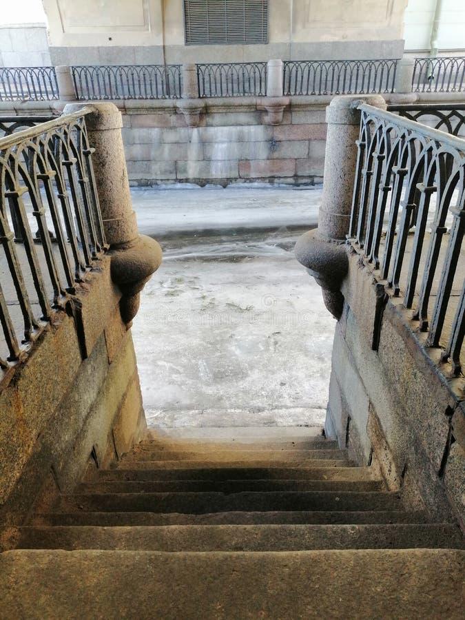 Спуск на старые шаги к замороженному каналу стоковое изображение rf