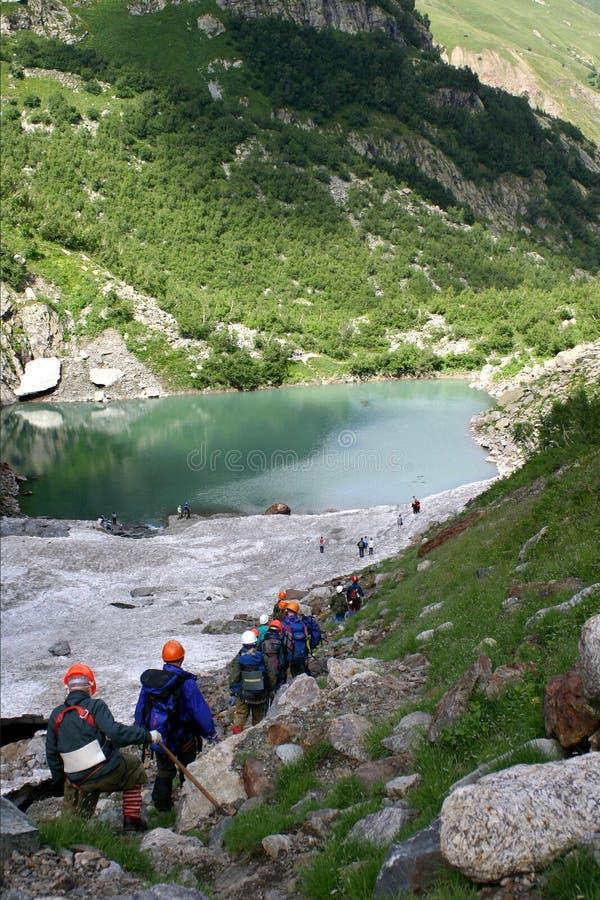 Спуск туристов к красивому озеру около Dombai стоковое фото