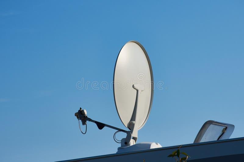 Спутниковая антенна-тарелка против голубого неба стоковое изображение