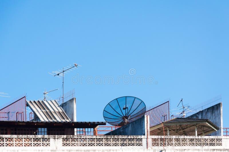 Спутниковая антенна-тарелка и антенна телевидения на старом здании с предпосылкой голубого неба стоковая фотография