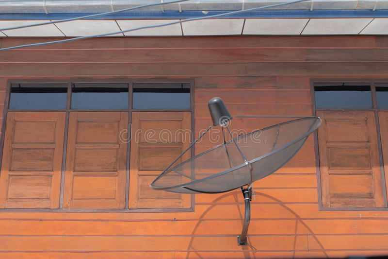 Спутниковая антенна-тарелка на стене с окном стоковое фото rf