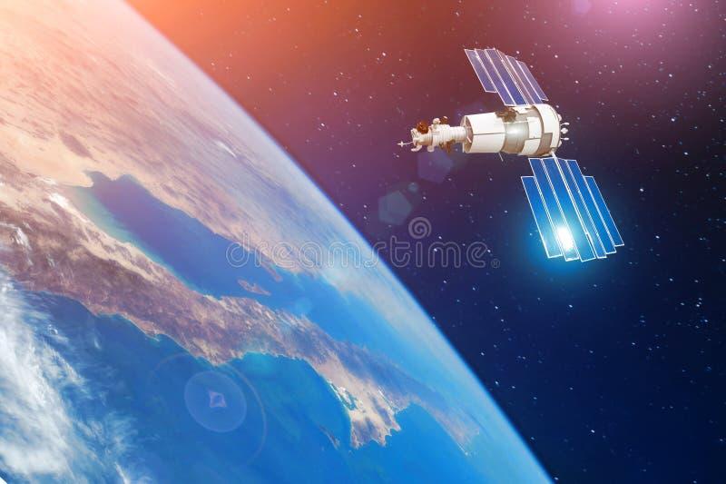 Спутник связи космоса в орбите вокруг земли Элементы этого изображения поставленные NASA стоковые фото