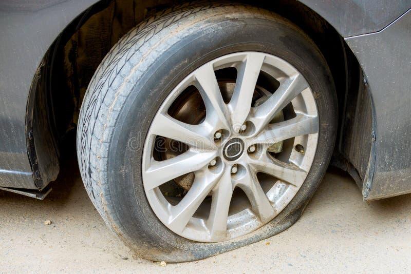 Спущенная шина колеса автомобиля на дороге сломанный аварией фокус водителя автомобиля около отражательного предупреждения тельня стоковые фото
