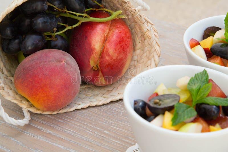 Сплетенная корзина с персиками и виноградинами стоковая фотография rf