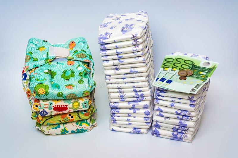 Сравните многоразовые пеленки ткани с кучей устранимых пеленок стоковое изображение