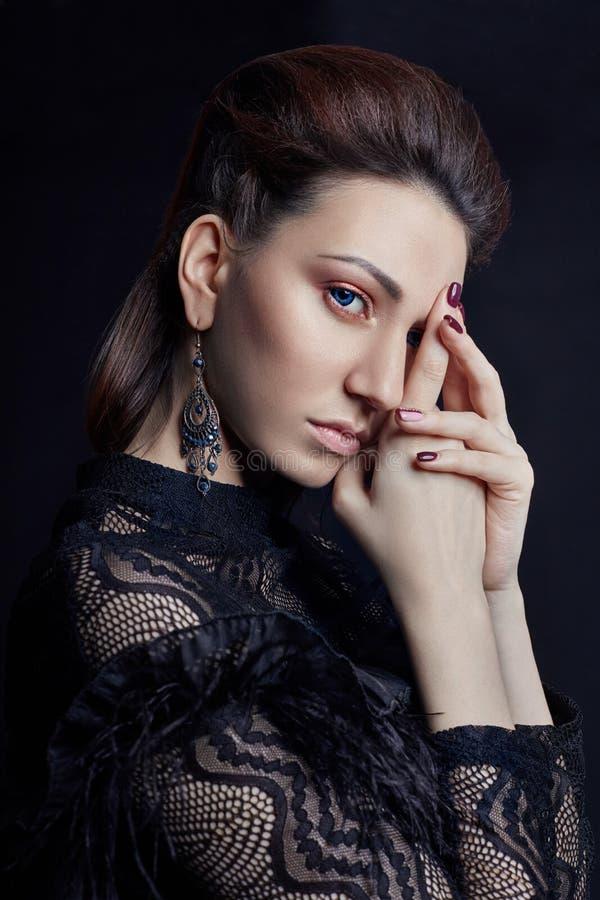 Сравните портрет женщины моды с большими голубыми глазами на темной предпосылке в черном платье Симпатичная шикарная девушка пред стоковые фото