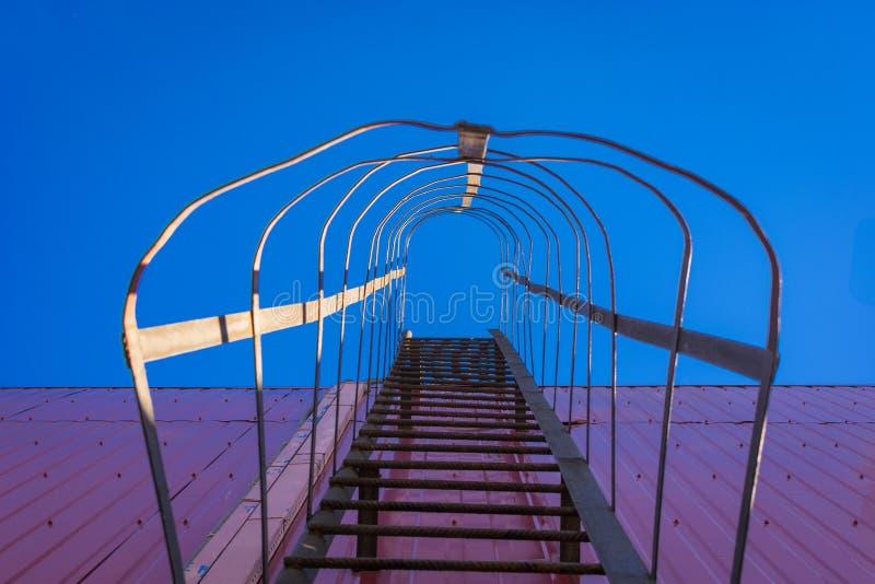 Сразу под съемкой металлической лестницы на стене против неба стоковые фотографии rf