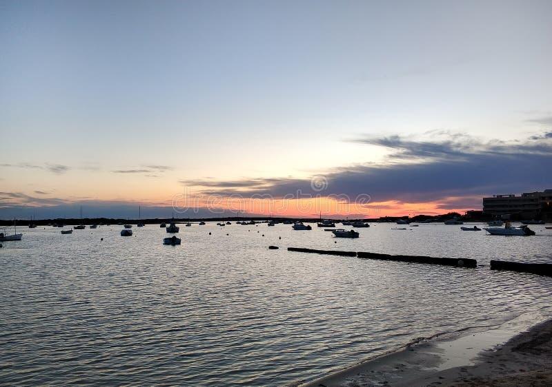 Средиземное море и причаленные сосуды на заходе солнца стоковые фотографии rf