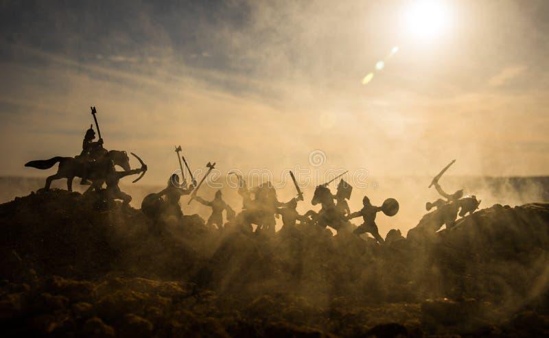 Средневековая батальная сцена с кавалерией и пехотой Силуэты диаграмм как отдельные объекты, бой между ратниками на fogg захода с стоковые фото
