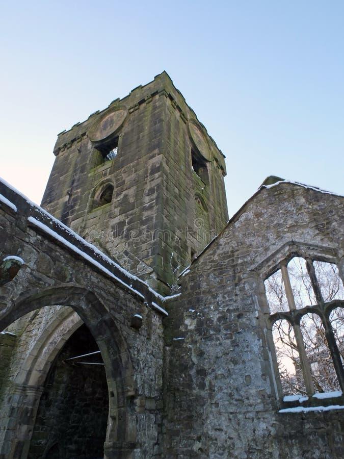 Средневековая загубленная церковь в heptonstall предусматриванном в снеге показывая своды и башню и окнах против голубого неба зи стоковые фотографии rf