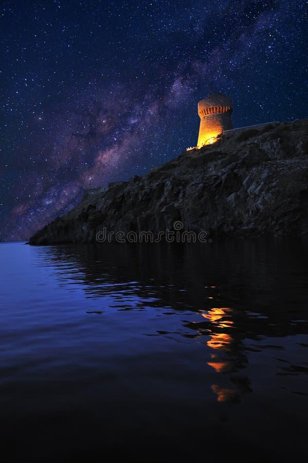 Средневековая сторожевая башня, тип городища, в острове Capraia, Италия под млечным путем стоковое фото