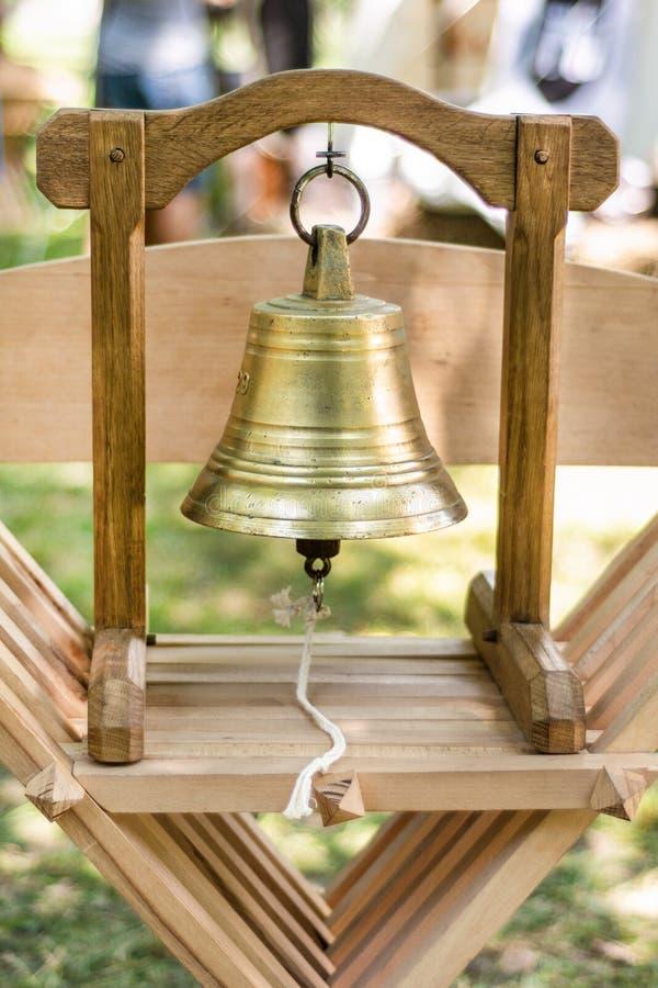 Средневековые латунные колокол и деревянная конструкция для пользы руки и звенеть металла на деревянном стуле стоковая фотография